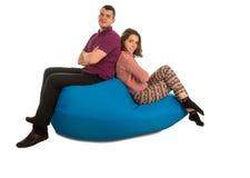 年轻可爱的男人和妇女坐蓝色装豆子小布袋沙发isol 库存照片