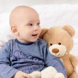 可爱的男婴坐床,使用与玩具涉及床 放松在床上的婴儿 库存照片