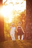 可爱的男孩和女孩日落的 免版税库存照片