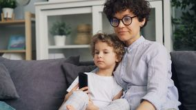 可爱的男孩和母亲年轻女人看着电视和在家谈话在沙发 影视素材