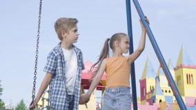 可爱的男孩和美女有长发的握手和谈话在摇摆附近,愉快地微笑 两三 股票录像