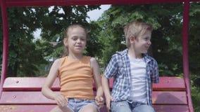 可爱的男孩和逗人喜爱的女孩坐摇摆关闭在公园,跳舞,获得看的乐趣秘密审议户外 A 股票视频