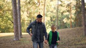 可爱的男孩在有他握他的手的爱恋的父亲的森林里走,有胡子的年轻人谈话并且打手势 股票录像