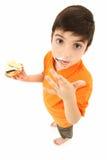 可爱的男孩舔chocolated的手指  免版税库存照片