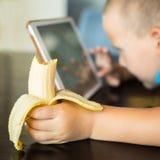 可爱的男孩,吃他的香蕉,当观看在片剂时的电影 免版税图库摄影