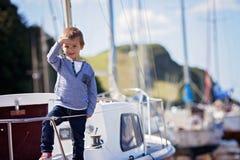 可爱的男孩,坐在港口的一条小船,低潮 免版税库存照片