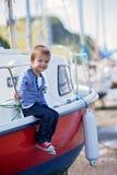 可爱的男孩,坐在港口的一条小船,低潮 库存图片