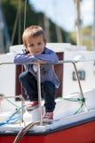 可爱的男孩,坐在港口的一条小船,低潮 图库摄影