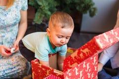 可爱的男孩画象有调查他们中的一个的giftboxes的 免版税库存照片