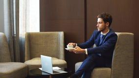 可爱的男性从在新的扣人心弦的项目的咖啡馆遥远地工作的年轻起始的enterpreneur,他喝专业咖啡 影视素材