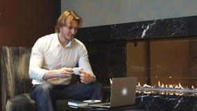 可爱的男性从在新的扣人心弦的项目的咖啡馆遥远地工作的年轻起始的enterpreneur,他喝专业咖啡 股票视频