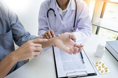 可爱的男性医生审查的谈论报告与遭受在诊所的背部疼痛的按摩患者 库存图片
