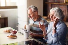 可爱的男性和女性领抚恤金者食用早餐在厨房 库存照片