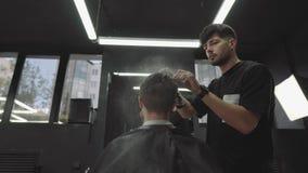 可爱的男性得到在理发店的现代理发 理发师由浪花弄湿头发并且梳他们 手扶的射击 4K 股票视频