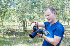 可爱的男性摄影师画象在工作看对照相机 调遣结构树 有一台DSLR照相机的年轻人在手上 一个人po 免版税库存图片