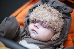 可爱的男婴在冬天在婴儿推车给睡觉穿衣 免版税库存图片