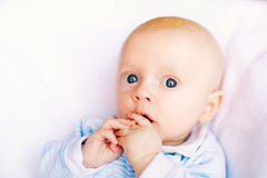 可爱的男婴在白色晴朗的卧室 免版税库存图片