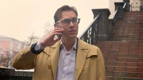 可爱的白种人人特写镜头有在电话被干扰的和担心的等待的一个电话在公园在秋天 影视素材
