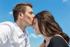 年轻可爱的白种人夫妇人亲吻前额的妇女 免版税库存照片