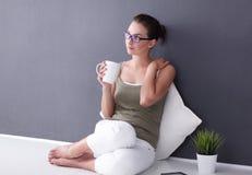 可爱的白种人女孩坐与杯子和片剂的地板在墙壁附近 免版税库存照片