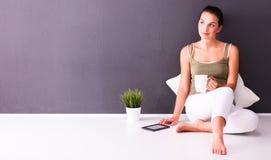 可爱的白种人女孩坐与杯子和片剂的地板在墙壁附近 免版税图库摄影