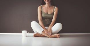 可爱的白种人女孩坐与杯子和片剂的地板在墙壁附近 库存图片