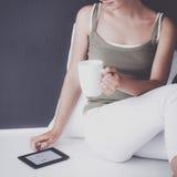 可爱的白种人女孩坐与杯子和片剂的地板在墙壁附近 免版税库存图片