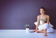 可爱的白种人女孩坐与杯子和片剂的地板在墙壁附近 库存照片