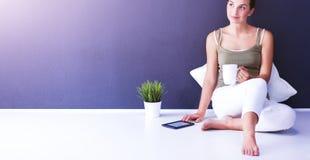 可爱的白种人女孩坐与杯子和片剂的地板在墙壁附近 图库摄影