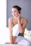 可爱的白种人女孩坐与电话的地板 免版税库存照片