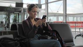 可爱的白种人女性在机场终端时使用一个手机,当坐 等待的概念 股票录像