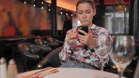 可爱的白种人女性在餐馆时使用一个手机,当坐 等待命令的概念 ? 股票录像