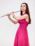 可爱的白种人妇女使用在银色长笛的长笛演奏家 免版税库存照片