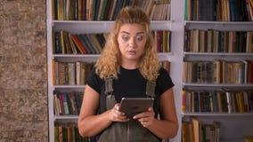 可爱的白种人白肤金发的女性在于键入时集中的图书馆里移动她的片剂,当站立在书旁边 影视素材