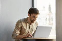 可爱的白种人自由职业者的男性画象在努力研究他的在咖啡馆的便携式计算机的便衣的以愉快 图库摄影