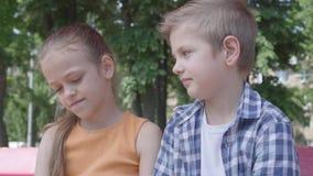 可爱的白肤金发的一个俏丽的女孩的男孩亲吻的面颊画象坐在操场的摇摆 女孩是害羞的 A 影视素材