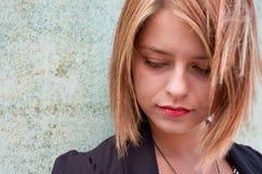 可爱的白肤金发的具体女孩周道的墙&# 免版税图库摄影
