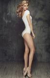 可爱的白肤金发的夫人佩带的高脚跟鞋子 免版税图库摄影