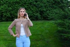 可爱的白肤金发的夫人在手中谈话在电话和举行它, smi 免版税图库摄影