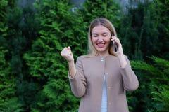 可爱的白肤金发的夫人在手中谈话在电话和举行它, smi 免版税库存照片