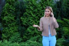 可爱的白肤金发的夫人在手中谈话在电话和举行它, smi 库存图片