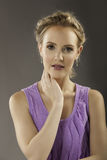 可爱的白肤金发的夫人画象紫色的 免版税库存照片