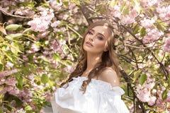 可爱的白肤金发的女孩在开花的庭院里 免版税库存图片