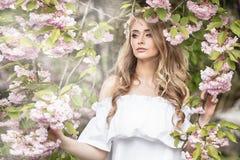 可爱的白肤金发的女孩在开花的庭院里 库存照片