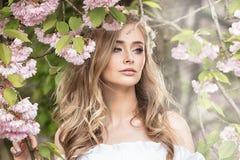 可爱的白肤金发的女孩在开花的庭院里 库存图片