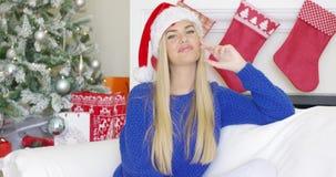 可爱的白肤金发的女孩坐沙发在圣诞老人帽子 影视素材
