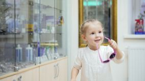 可爱的白肤金发的女孩跳舞和在医疗商店-在诊所的购物要求妈妈买桃红色玻璃 股票视频
