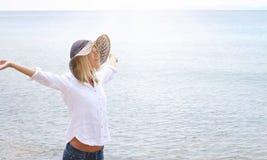 可爱的白肤金发的妇女佩带的白色衬衣和草帽呼吸满意对被举的胳膊 查出的黑色概念自由 朦胧的轻的图象 免版税库存照片