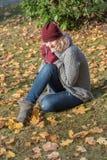 可爱的白肤金发的妇女在一个秋季公园 免版税库存图片