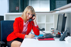 可爱的白肤金发的妇女在办公室谈话与电话 免版税库存图片
